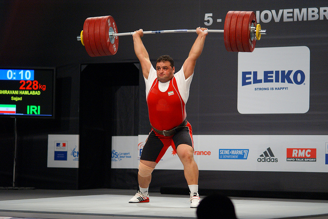 A weightlifter holds a heavy bar laden with weights above his head.