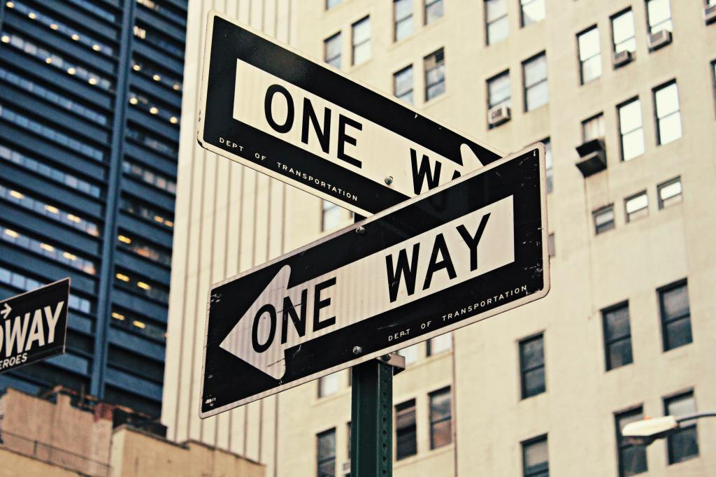 Street signs indicating one way - pointing in different directions