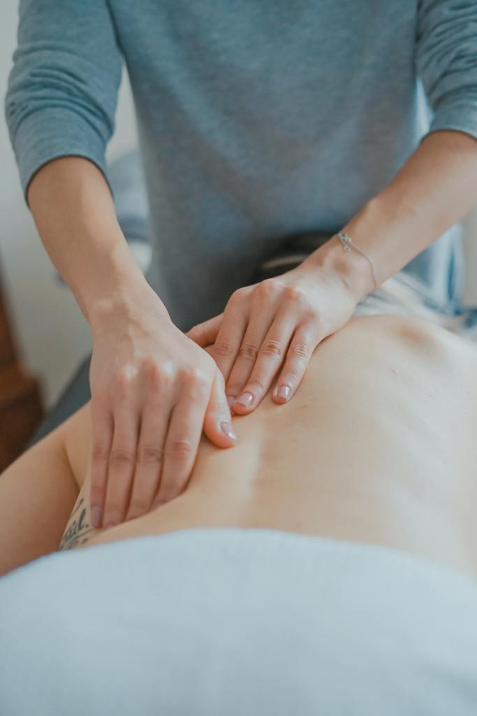 Image shows hands massaging someone's back