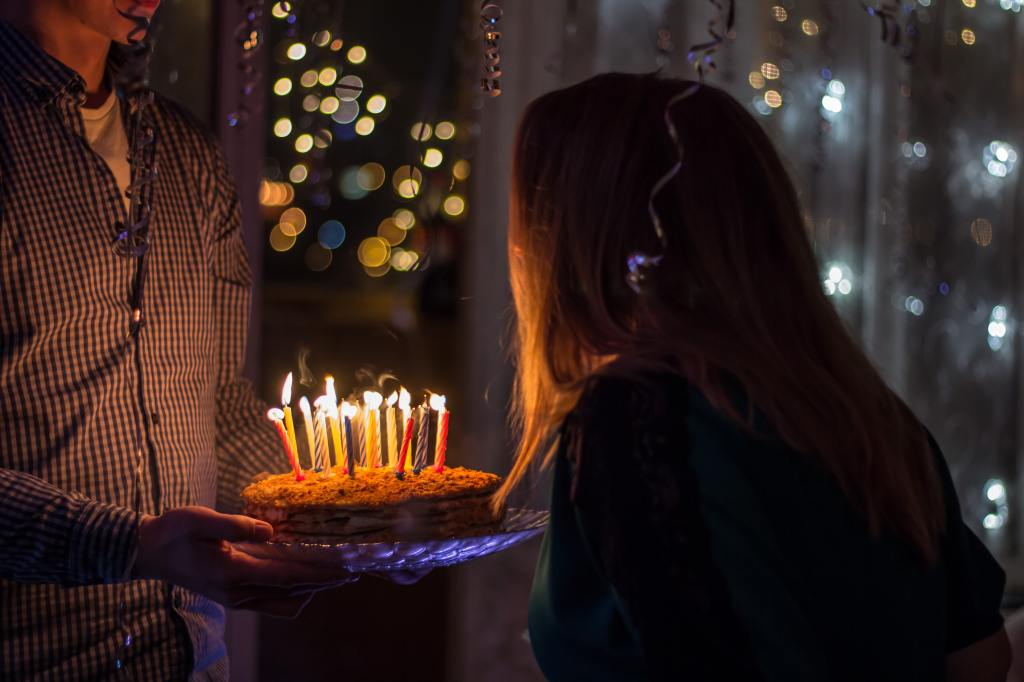 A long haired person leans to blow out candles on a cake held by someone in a shirt